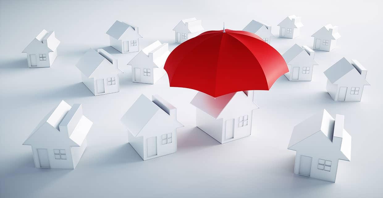 Eigenheim versichern, weißes Haus, roter Schirm